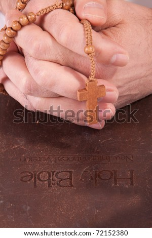 A person holding cross on the bible praying