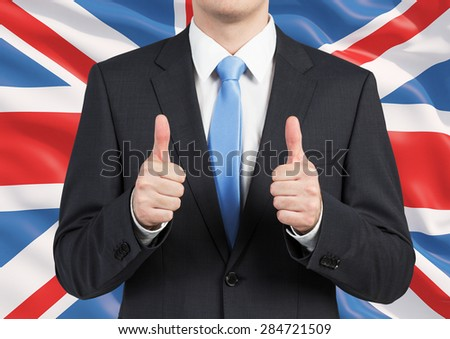 A person in a suit thumbs up. Great Britain flag as a background. - stock photo
