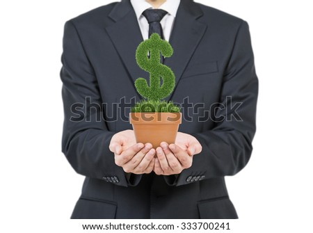 A person in formal suit holds a flowerpot with grass green dollar sign. Isolated on white background. - stock photo