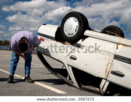 A person inspecting damage to an overturned car - stock photo