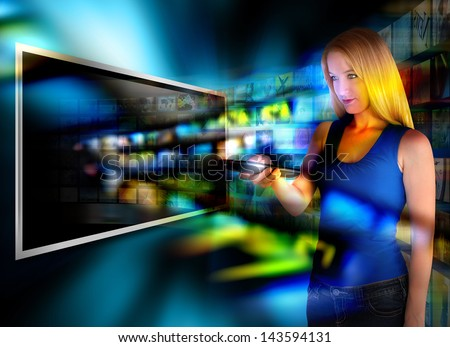 A person is holding a remote control and watching television on a widescreen tv with video images coming out on a black background. - stock photo
