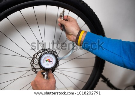 A person is inflating a bicycle wheel with the help of compressed air and a pressure gauge. Wheel and hand seen in the background in soft focus.