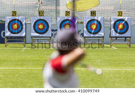 A person is shooting with recurve bow on a target during an archery competition. Focus on the targets. - stock photo