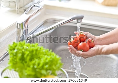 A person is washing a handful of tomatoes under the kitchen faucet. - stock photo
