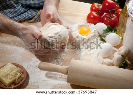 A person kneading dough on wooden table with other produces on it