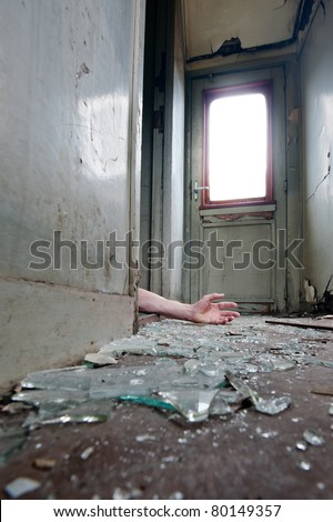 A person lying in doorway unconscious in messy environment. - stock photo