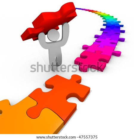 A person places the final piece in the puzzle to solve it - stock photo