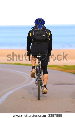 A person riding a bicycle on a seashore recreation trail