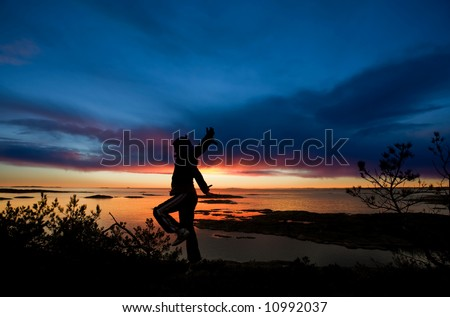 A person running by the ocean raising their arms in celebration