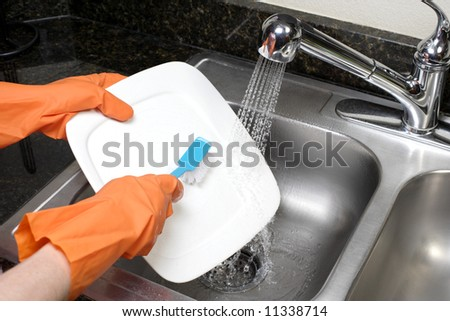 A person scrubs a dish in the kitchen sink - stock photo