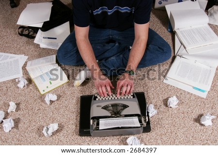 A person surrounded by reference materials works at  a typewriter. - stock photo