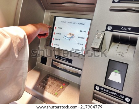 A person takes money at an ATM bank