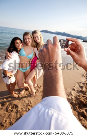 A person taking a picture of three women with a camera phone.  Shallow depth of field, focus on camera - stock photo