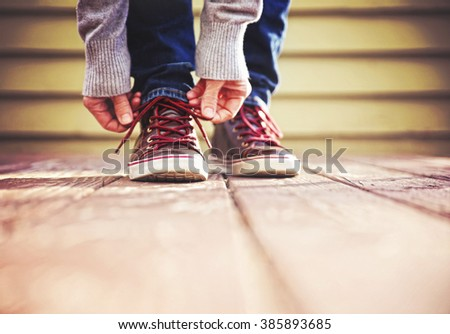 a person tying their shoes on their feet outside on a stained wooden deck toned with a retro vintage filter instagram app or action effect  - stock photo