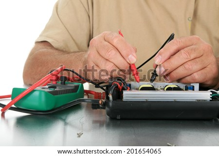 a person uses a voltage meter to check for dead circuits, faults and shorts in an electronic device.  - stock photo