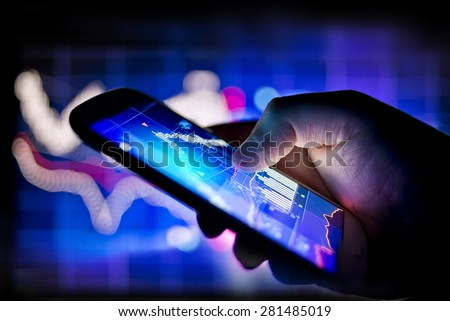 A person using a mobile phone to track real time stocks and shares data - stock photo