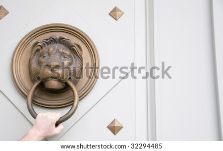A person using the brass lion door knock to get in.