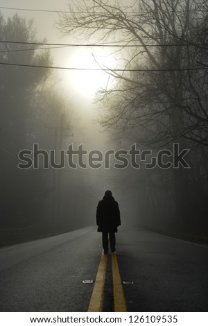 A person walk into the misty foggy forest road in a dramatic  sunrise scene - stock photo