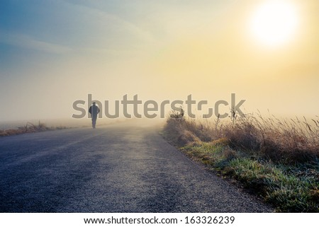 A person walk into the misty foggy road in a dramatic mystic sunrise scene with abstract colors - stock photo