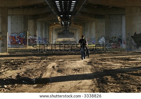a person walking under anh old bridge, graffiti drawings all around him