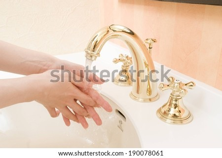 A person washing their hands with a gold faucet. - stock photo