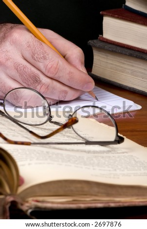 A person works on a paper with open books and glasses on a table - stock photo