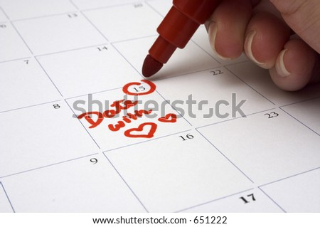 "A person writing down the appointment for a date with a loved one on the calendar. Shallow depth-of field - focused on the words ""Date with"" - stock photo"