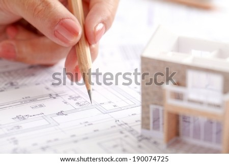 A person writing on a set of blueprints. - stock photo