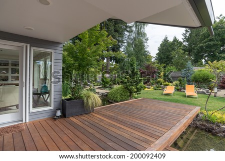 A perspective view of a contemporary Pacific Northwest home with a deck bridging a pond that leads to a pair of modern yellow loungers in a landscaped yard.  - stock photo