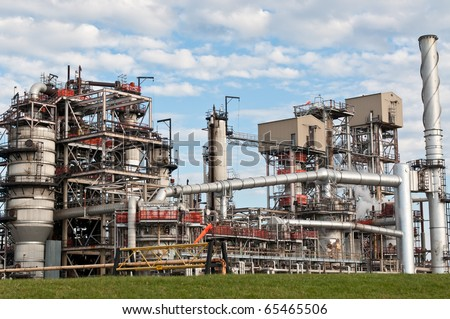 A petrochemical refinery plant with pipes and cooling towers. - stock photo