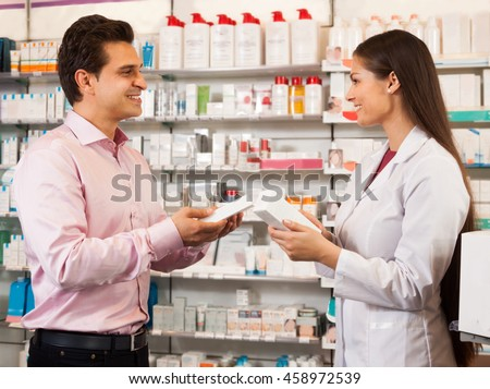 A  pharmacist woman in a white coat offers the visitor a cure at the chemists shop