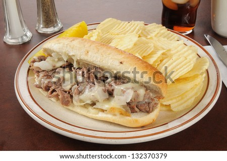 A Philly cheese steak sandwich with french fries and cola - stock photo