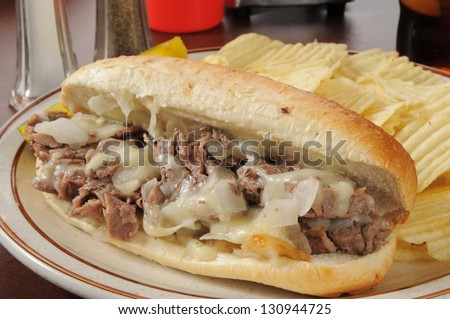 A philly cheese steak sandwich with potato chips - stock photo