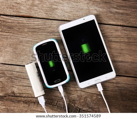 a phone and a tablet being charged with a power hub bank toned with a retro vintage instagram filter app or action effect  - stock photo