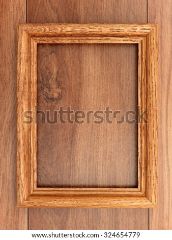 A photo frame on a wooden shelf