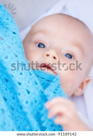 A photo of a beautiful baby boy in his bed - stock photo