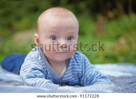 A photo of a beautiful baby boy outdoor in sunshine - stock photo