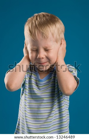A photo of a boy closed his ears and eyes tight - stock photo