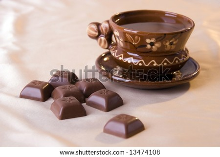 a photo of a brown clay cup and chocolate