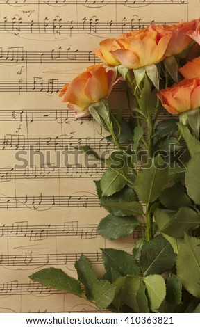 A photo of a bunch of orange colored tea roses on a background of aged sheet music, slightly toned - stock photo