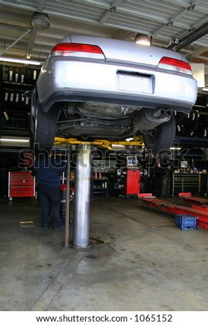 A photo of a car on a lift getting repaired - stock photo