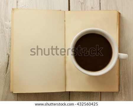 A photo of a cup of dark coffee on a page of an open old book (with copyspace), shot from above - stock photo