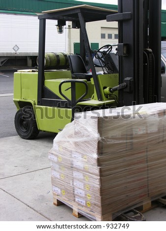 A photo of a forklift unloading a crate with a warehouse in the background - stock photo