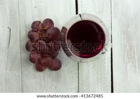 A photo of a glass of red wine with a bunch of grapes, shot from above on a light blue wooden background texture, with copyspace - stock photo