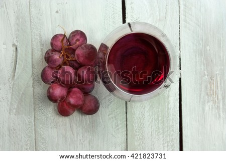 A photo of a glass of red wine with a bunch of grapes, shot from above on a light blue wooden background texture, enriched by a layer of watercolor, with copyspace - stock photo