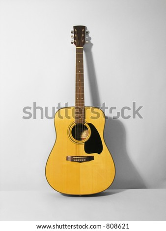 A photo of a guitar leaning against the wall - stock photo