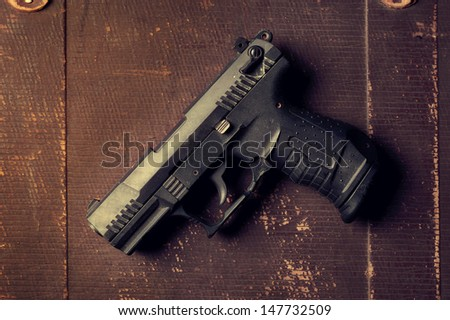 A photo of a gun on a old grunge surface - stock photo