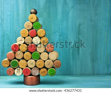 A photo of a handmade Christmas tree, made up of painted wine corks; 'Winemaker's Christmas' concept; shot on a turquoise blue background with a place for text - stock photo