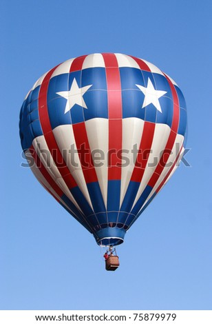 A photo of a hot air balloon during a balloon race over the skies of Florida. The balloon has the colors of the United State Flag right down to the stars. - stock photo