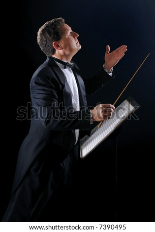 A photo of a music conductor wearing a tuxedo, conducting an orchestra on a black background